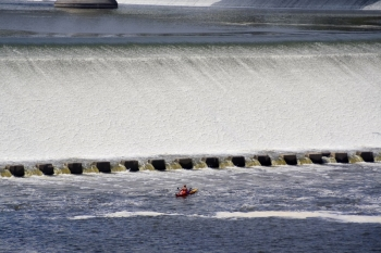 Photo of a kayaker in front of a dam.