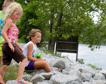 Photo of children sitting on rocks beside the water.