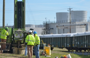 Drill rig operators prepare to retrieve a sample to be used to determine the location of the wells to optimize pump-and-treat operations at the Paducah Site's northeast plume.