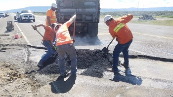 Workers with Watts Construction, a small business subcontractor to site services provider MSA, help with asphalt repairs on the site.