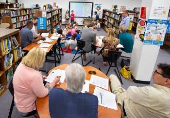 """Oak Ridge Office of Environmental Management employees listen and give tips to third-graders presenting their """"Schools around the World"""" project."""