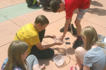 Middle school students learn about solar power out in the sunshine on Energy Day