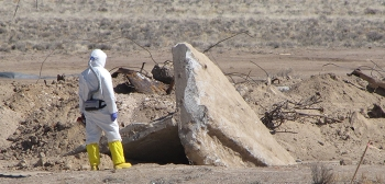 A radiological control technician prepares to survey concrete debris uncovered during excavation of soil.
