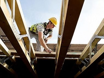 A construction worker framing a house.