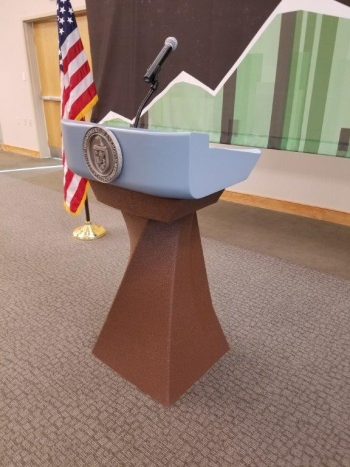 a 3D printed podium, and an american flag in the background.