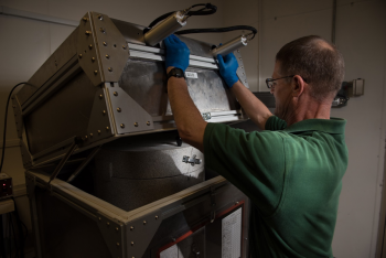 Scientist Mike Cantaloub uses a piece of equipment designed by WSU students at one of PNNL's laboratories.