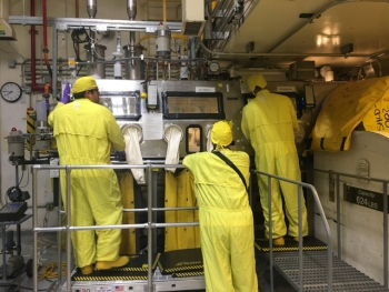 Los Alamos National Security workers use the glove box in the Waste Characterization, Repackaging and Reduction Facility.
