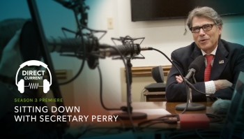 """A photo of Secretary Perry sitting in a recording studio, with the logo for """"direct current"""" and the text """"Sitting down with Secretary Perry"""""""