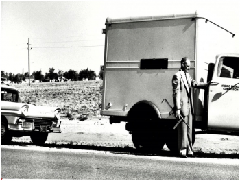 An Atomic Energy Commission courier in the late 1950s armed with an M3 submachine gun at the cab of a bobtail truck that carried high explosives. Behind the truck is a Ford ranch wagon used as an escort vehicle.