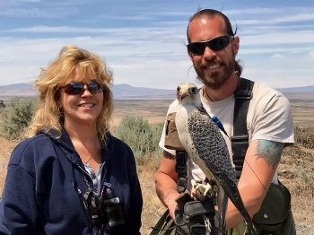 Hanford Site Radiological Control Technician Kathy Keelean, left, conducted a radiological survey on Jack the falcon. His handler, Chase H. Delles, is at right.