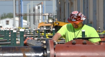 A worker with LATA-Kentucky, predecessor to FFS and FRNP, works on pipes leading to an above-ground treatment system that was part of an electrical-resistance-heating groundwater source remediation project adjacent to the C-400 building.