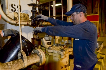 An operator removes a filter in a trap during lubrication oil removal from the process buildings.