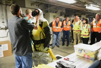 DOE Under Secretary for Science Paul Dabbar and others watch a Fluor Idaho employee don personal protective equipment prior to entering an Advanced Mixed Waste Treatment Project boxline to perform a criticality cleanout.