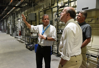 Fluor-Idaho Integrated Waste Treatment Unit (IWTU) Operations Manager Craig Olson, left, and DOE IWTU Project Manager Kevin O'Neill, behind, brief DOE Under Secretary for Science Paul Dabbar at IWTU.