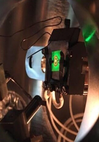 A green LED being electrically powered inside an ultra-high vacuum electron emission spectroscopy chamber.