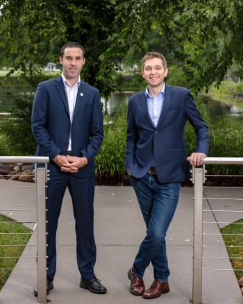 a photo of two men standing in front of a small lake.