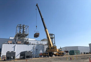 Workers remove an old chiller from atop the Advanced Mixed Waste Treatment Project's treatment facility.