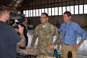 Col. Theodore Breuker, commander of security forces at Kirtland Air Force Base in Albuquerque, left, and Robert Suminsby, manager of the OST Office of Mission Operations, listen to an OST federal agent describe equipment used by agents.