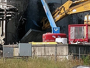 Heavy equipment lowers the 60-ton transfer tunnel shield door to the ground.