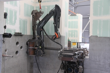 Crews attached a remote excavator to the wall at the 324 Building mockup. Installing the equipment required the precise drilling of support holes.