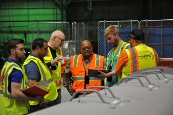 """FBP's Rob Allyn demonstrates how to use a tablet to launch the Radpiper robot. From left, EM Fellow Michael DiBono; CMU's David Kohanbash and William """"Red"""" Whittaker; Rod Rimando, Dir of EM's Tech Dev Office; and FBP's Allyn and Brian Summers."""