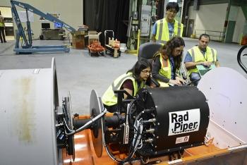 Carnegie Mellon University (CMU) roboticists make adjustments to the program to move the robot. From left, Siri Maley, Heather Jones, Kenji Yonekawa, and David Kohanbash.