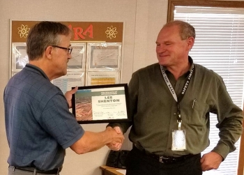 Lee Shenton, left, accepts a certificate of appreciation from Moab Federal Cleanup Director Russell McCallister.