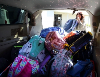 Adina Eliassian loads van with backpacks