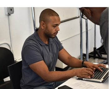 Photo of a man typing on a laptop computer.
