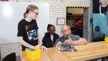 Sprocket Director Jimi Gwinn, right, uses circuit boards to teach Paducah students Chris McVickers, left, and Miya Patterson about computer technology.