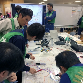 Japanese public safety team members plan out an evacuation route in the offsite center during the exercise.