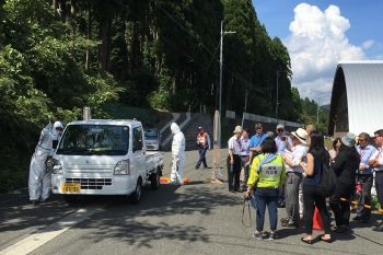 The observer group watching a vehicle pass through a radiation-screening station during the exercise.