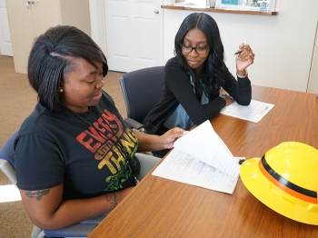 Savannah River Remediation (SRR) labor relations summer intern Mikhaela Kelson (right) oversaw the onboarding paperwork process with newly hired SRR Construction Laborer Sherlaine Flournoy.