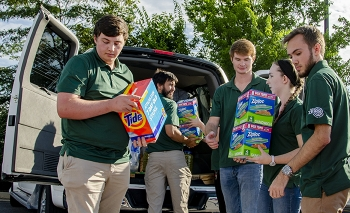 Supporting a Paducah Site community service outreach, college interns load supplies donated by the annual Feds Feed Families food drive for a western Kentucky charity.