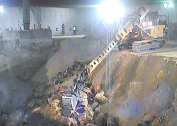 Crews use an excavator with an extended boom to exhume buried waste at the Accelerated Retrieval Project facilities at the Idaho National Laboratory Site.