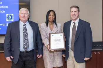 Leslie Winfield of the Nevada Field Office, left, and Donnie Schuessler with Mission Support and Test Services, right, accept the 2018 Federal Aviation Program – Small Category award from Carolyn Austin-Diggs of the General Services Administration.
