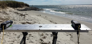 Photo of a table set up on a beach with two cameras on it.