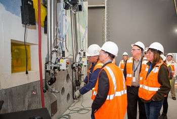 Equipment operator, Dwight Bowman, demonstrates a manipulator moving objects in the mock-up of a 324 Building hot cell for DOE Chief Financial Officer John Vonglis, Richland Operations Office Manager Doug Shoop, and EM Assistant Secretary Anne White.