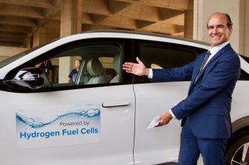 Under Secretary of Energy Mark Menezes in front of a fuel cell electric car