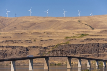 Photo of a series of wind turbines on top of a tall, earthen hill.