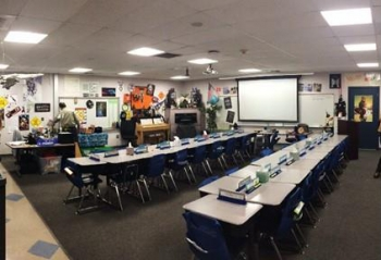 A photo of a classroom with desk and chair, and overhead lighting.