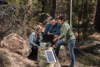 Los Alamos National Laboratory researchers Janette Frigo, Jim Krone and Alex Saari configure a stormwater runoff sensor node in the field.