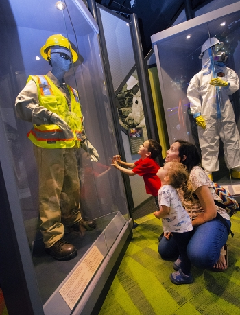 Exhibit of equipment and suits that keep employees safe as they perform cleanup.