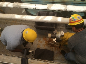 Workers practice waste transfer line modification work in a mock-up area.