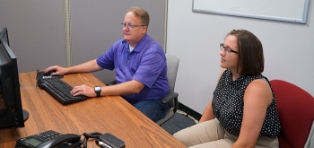 Savannah River Remediation Principal Cyber Specialist Sean Nixon, left, mentors high school student Colleen Harmon on cybersecurity applications.