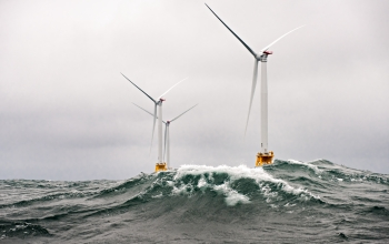 Photo of three offshore wind turbines in the open ocean, with waves cresting against them.