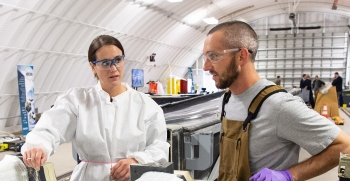 Two researchers work on a mold for a wind blade turbine.