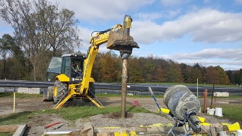 A backhoe is used to pull the well pump and casing from the ground after workers stabilized the casing with grout.