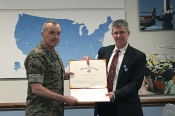 Keith Hamilton is presented with Department of Navy Superior Civilian Service Award by Major Gen. Vincent A. Coglianese, Marine Corps Installation Commander.