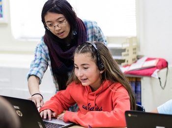 Los Alamos Lab researcher works with an elementary school student during an Hour of Code session.